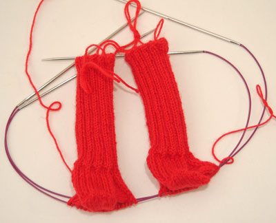 two at a time cuff down red baby socks, just past the gussets & ready to work down the foot